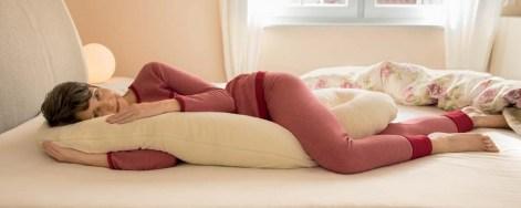 Frau mit Allround Lagerungskissen im Bett