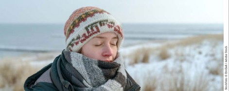 Frau mit Schal und Mütze am verschneiten Strand