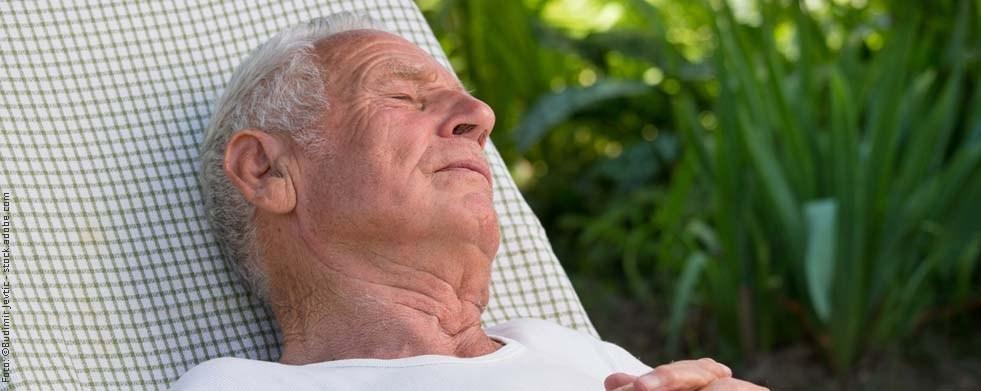 Älterer Mann schläft im Garten