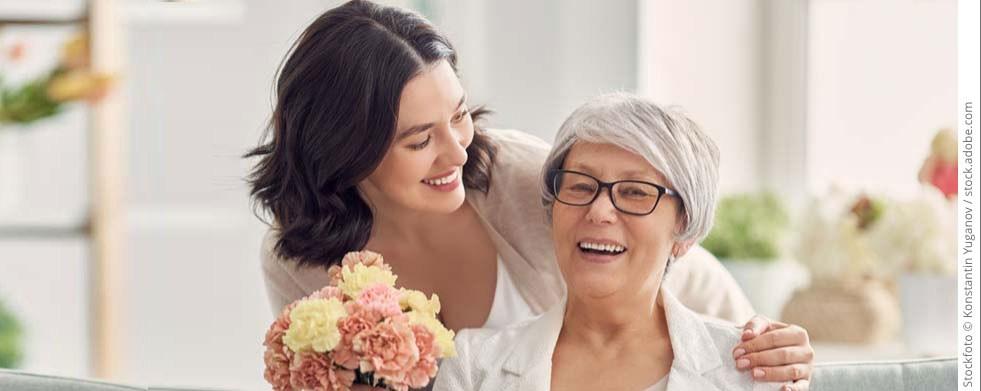 Frau überrascht Mutter mit Blumenstrauss