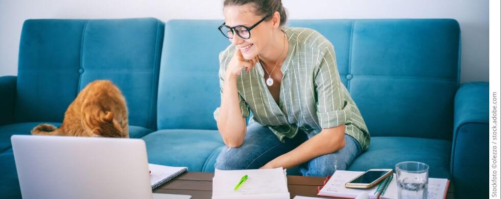 Frau sitzt auf Sofa mit Laptop und Unterlagen auf dem Tisch - Homeoffice