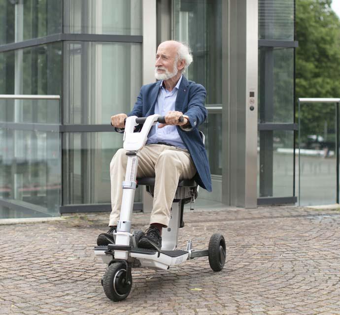 Mann auf dem faltbaren Elektromobil ATTO