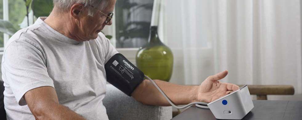 Mann mit Brille misst Blutdruck