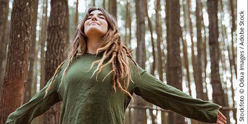 Frau mit ausgebreiteten Armen im Wald