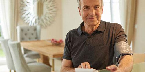 Mann mit Blutdruckmanschette am Arm
