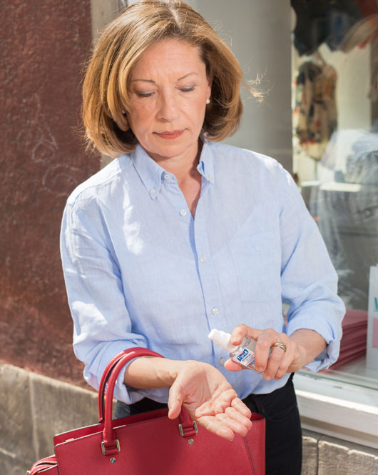ältere Frau nutzt Handdesinfektionsmittel