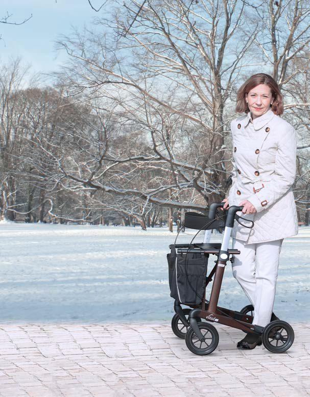 Frau geht am Rollator in Schneelandschaft