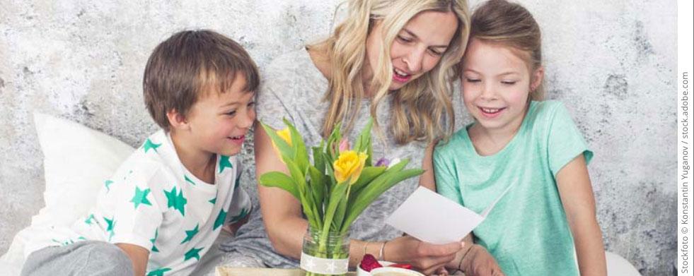 Frau mit zwei Kindern und Frühstückstablett und Blumen im Bett