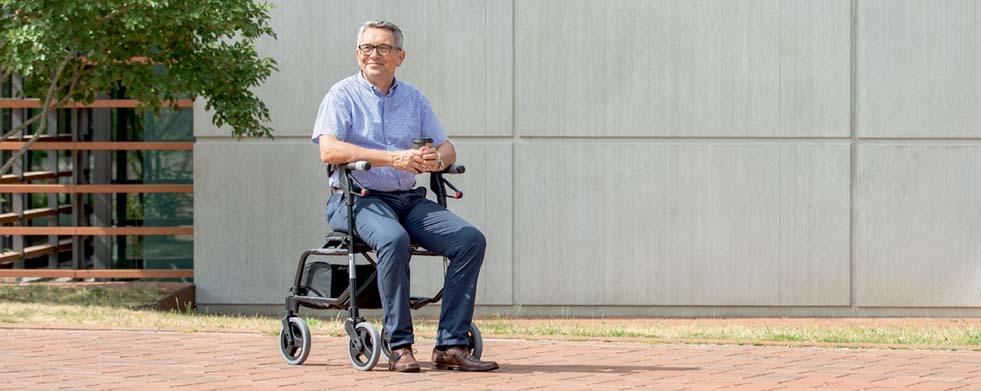 Mann sitzt auf Rollator Nexus