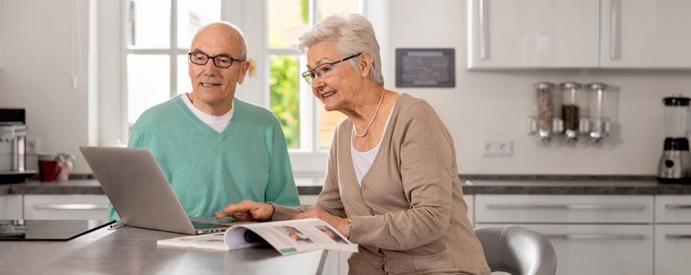 Paar mit Laptop in der Küche