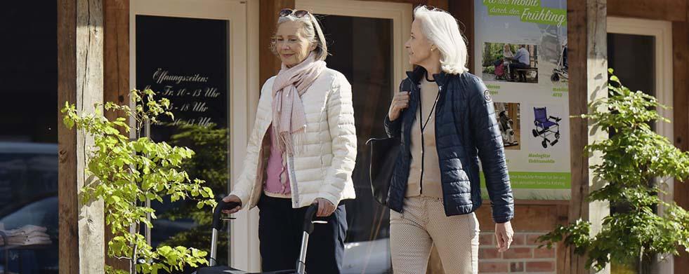Zwei Frauen mit Rollator in der Fußgängerzone